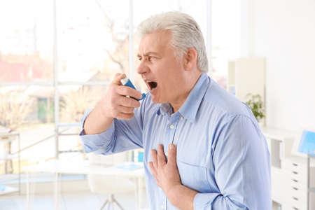 Elderly man using inhaler in clinic