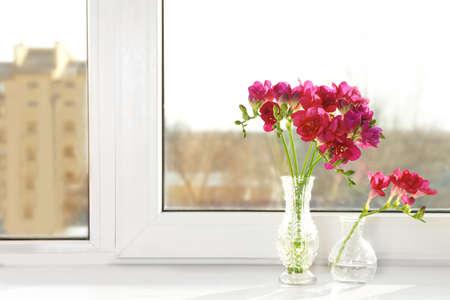 Vases with beautiful flowers on windowsill Stock Photo