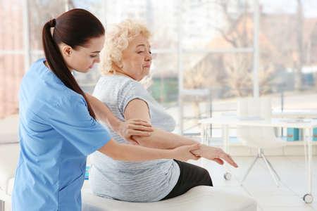 診療所でシニア女性を調べる女性整等職