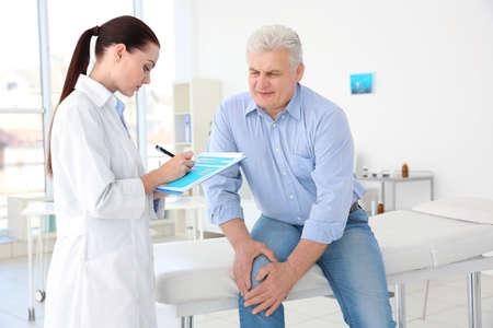 Kobieta ortopeda bada starszego mężczyznę w klinice