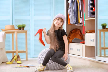 Cute little girl with fashionable shoes at home