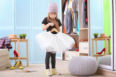 Cute little girl with fashionable clothes at home