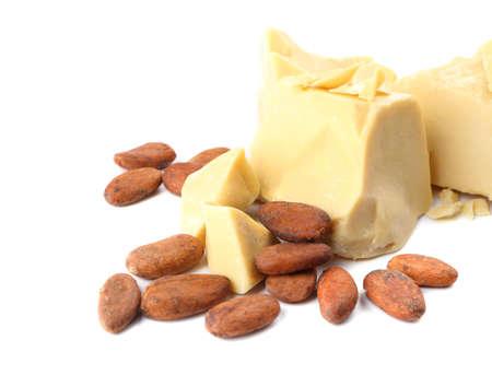 Stücke Kakaobutter und Bohnen auf weißem Hintergrund