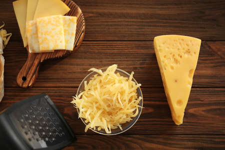 Bowl with grated cheese and piece on wooden table