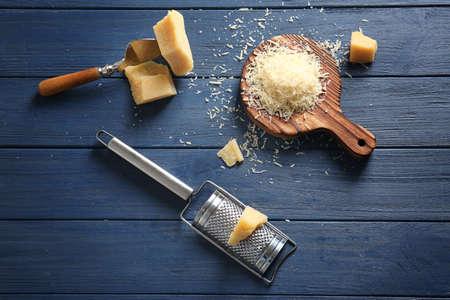 テーブルの上にチーズとおろし金が付いた木製のボード 写真素材