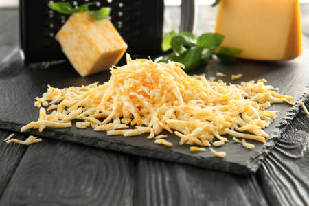 Slate plate with grated cheese on wooden table