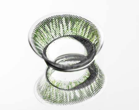 Green contact lens on light background with reflection
