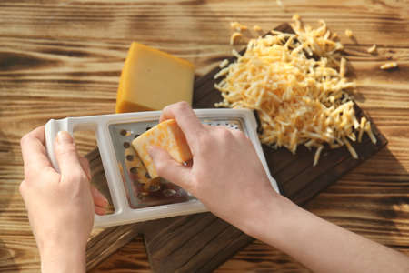 Woman grating cheese on wooden table Stock Photo