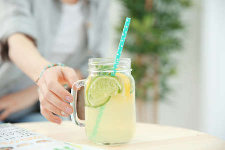 Hand of young woman taking jar of lemonade from table