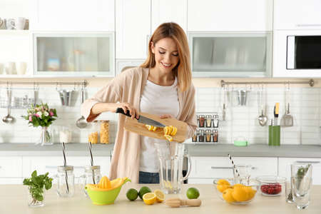 Beautiful young woman preparing lemonade in kitchen