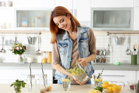 Beautiful young woman pouring lemonade into glass in kitchen