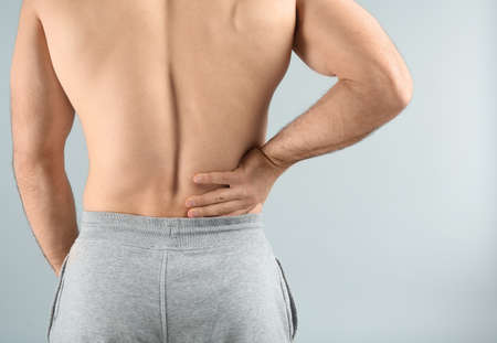 Young man suffering from back pain on light background, closeup