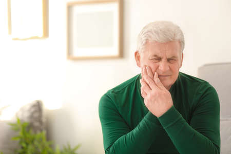 Mature man suffering from toothache at home