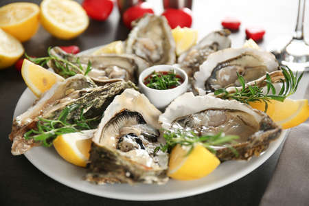 Tasty fresh oysters with sauce and sliced lemon on plate. Aphrodisiac food for increasing sexual desire
