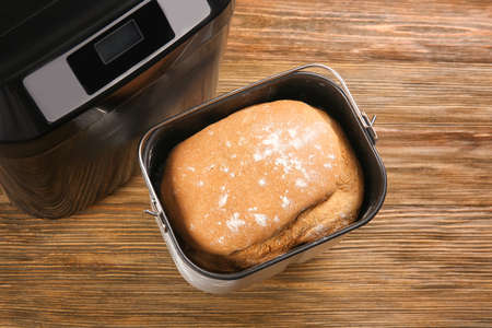 Baking pan with fresh homemade bread on wooden background