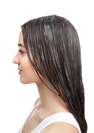Young woman with coconut oil applied onto hair, on white background Banco de Imagens