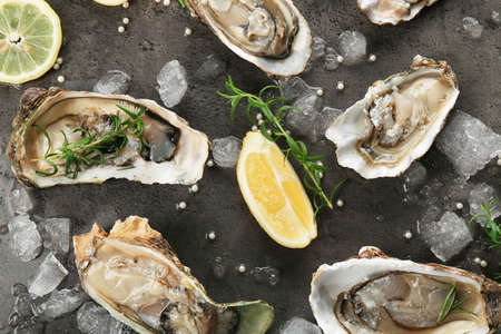 Tasty fresh oysters with sliced juicy lemon and ice on dark background. Aphrodisiac food for increasing sexual desire