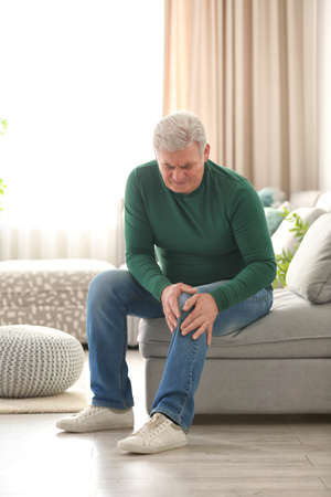Mature man suffering from knee pain at home Stock Photo