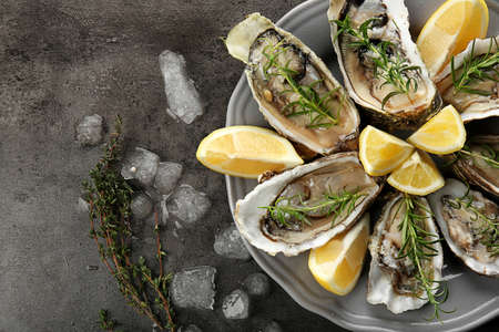 Tasty fresh oysters with sliced lemon on plate. Aphrodisiac food for increasing sexual desire