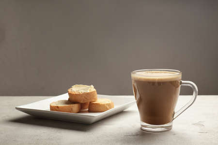 Composition with tasty butter coffee and toasts on grey table