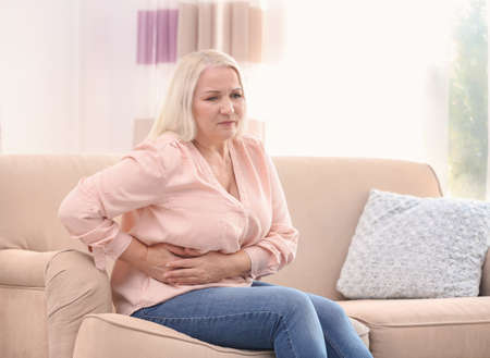 Mature woman suffering from stomach ache at home