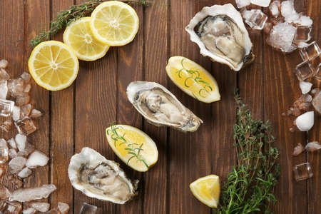 Tasty fresh oysters with sliced juicy lemon and ice on wooden background. Aphrodisiac food for increasing sexual desire Stock Photo
