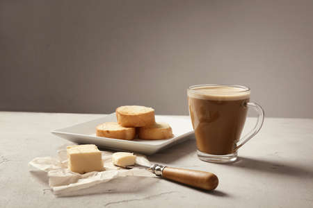 Composition with tasty butter coffee and toasts on table