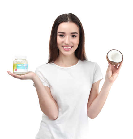 Beautiful young woman with jar of coconut oil on white background