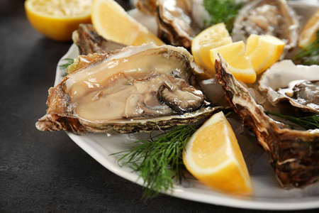 Tasty fresh oysters with juicy sliced lemon on plate. Aphrodisiac food for increasing sexual desire Stock Photo