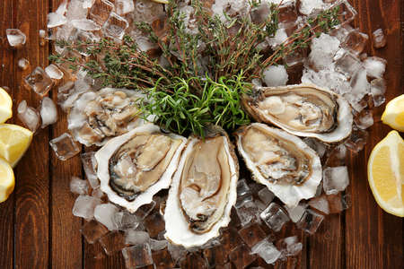 Composition with fresh tasty oysters, herbs and ice on wooden background. Aphrodisiac food for increasing sexual desire