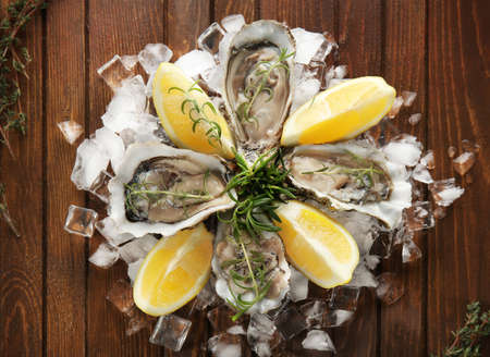 Tasty fresh oysters with sliced juicy lemon and ice on wooden background. Aphrodisiac food for increasing sexual desire Stockfoto