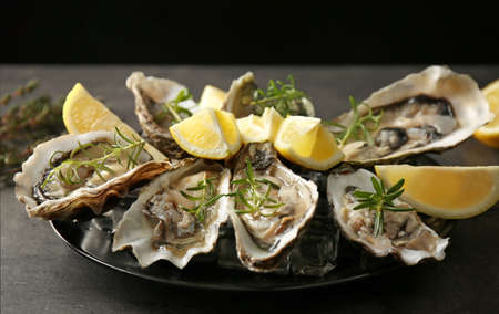 Tasty fresh oysters with sliced juicy lemon on plate. Aphrodisiac food for increasing sexual desire