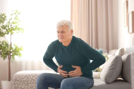 Mature man suffering from stomach ache at home Stockfoto