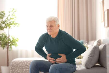 Mature man suffering from stomach ache at home Archivio Fotografico
