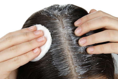 Young woman applying coconut oil onto hair, closeup Imagens