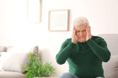 Mature man suffering from headache at home Stok Fotoğraf