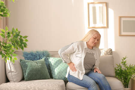 Mature woman suffering from pain in her side at home Stock Photo