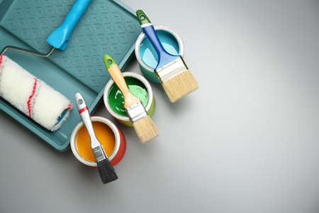 Paint cans, brushes, roller and tray on grey background Banco de Imagens