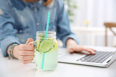 Young woman with lemonade and laptop in cafe, closeup