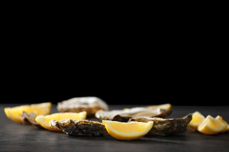 Tasty fresh oysters with sliced juicy lemon on dark background. Aphrodisiac food for increasing sexual desire