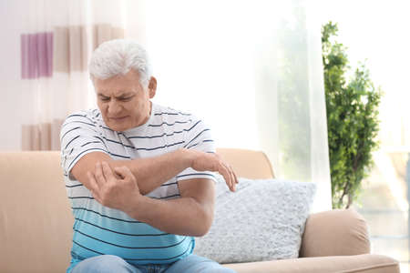 Mature man suffering from elbow pain at home