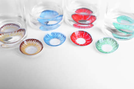 Color contact lenses and glass bottles on white background