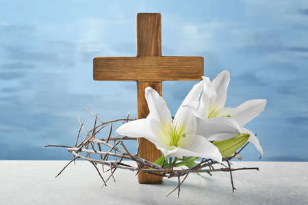 Crown of thorns, wooden cross and white lily on table Stock Photo
