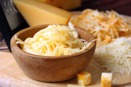 Wooden bowl with grated cheese on board