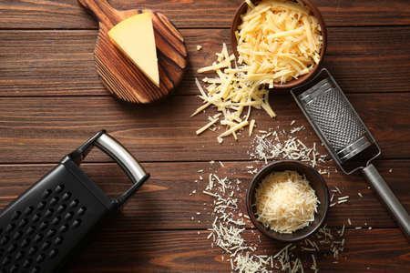 Graters, bowls with cheese and cutting board on wooden background