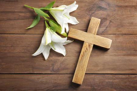 Croix en bois et lis blanc sur table% 00 Banque d'images