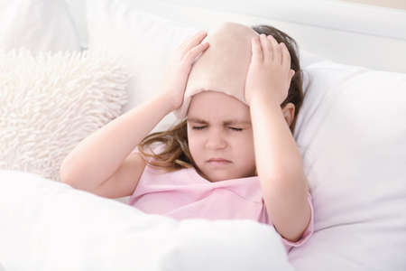 Little girl suffering from headache while lying in bed with compress Stock fotó