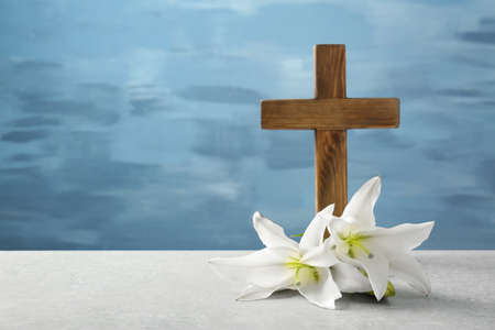 Wooden cross and white lily on table Banco de Imagens - 97709615
