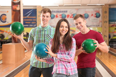 Happy friends playing bowling together