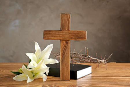 Corona de espinas, cruz de madera y lirio blanco en la mesa% 00